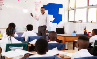 african male teacher teaching his pupils while standing