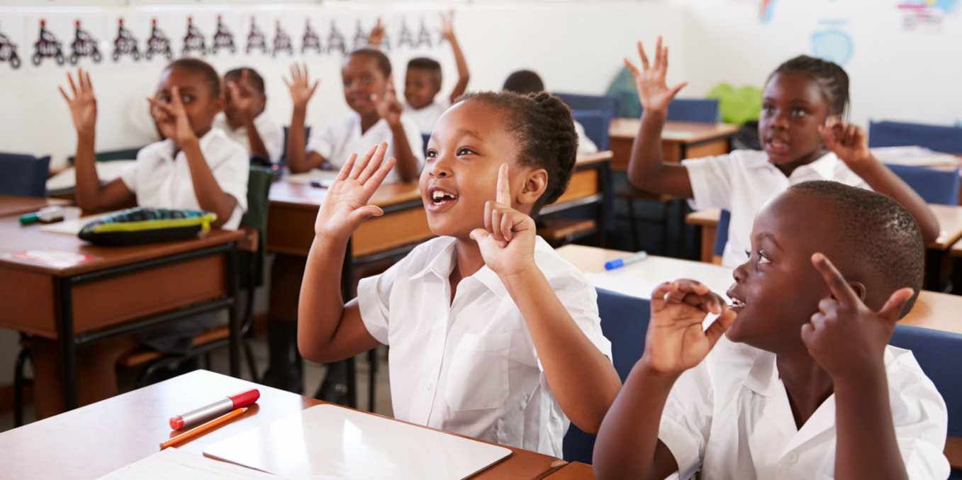 a group of african pupils raising their hands